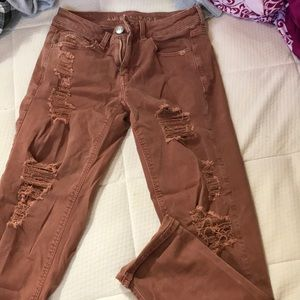 Rust colored ripped jeans